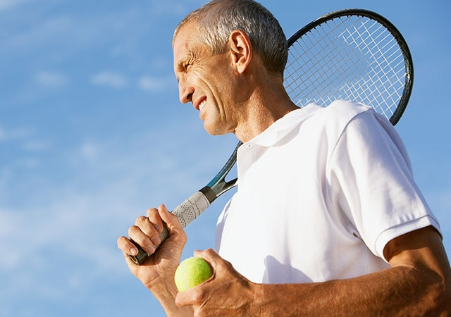 Photo of man holding tennis racket and ball