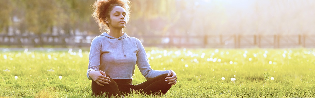 woman on grass meditating