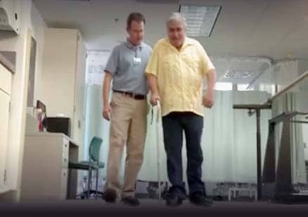 man helps patient walk with cane