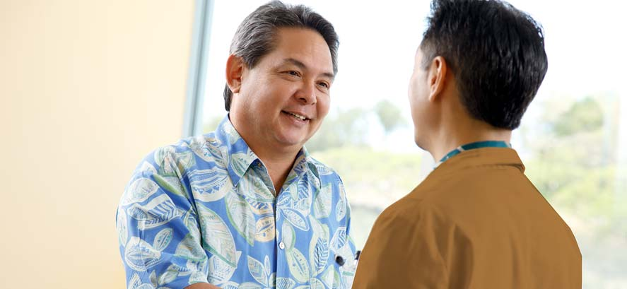 Middle age man in Hawaiian shirt talking with friend
