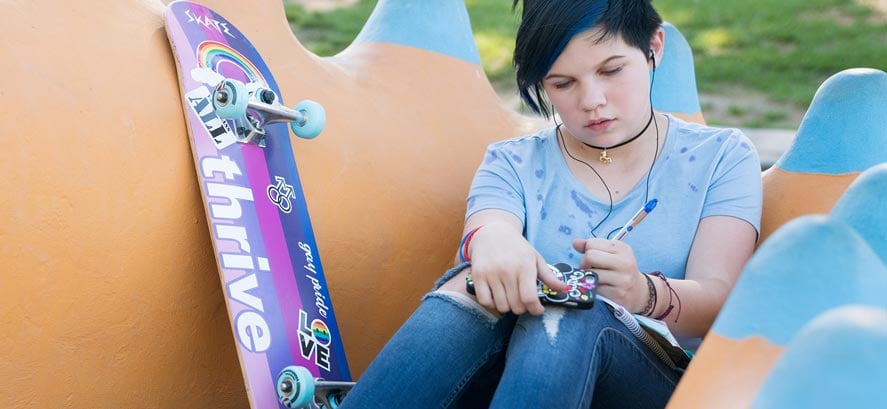 Teenage girl with blue hair writing in journal with skateboard