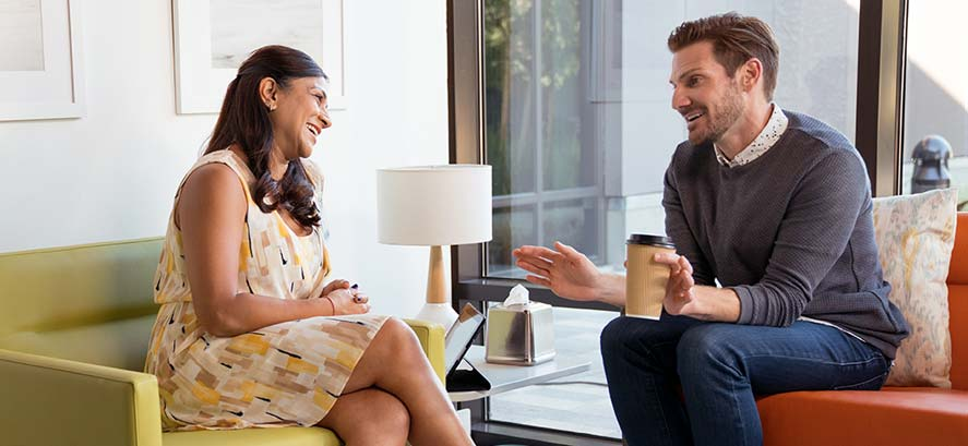 Woman and man talking over coffee in therapy