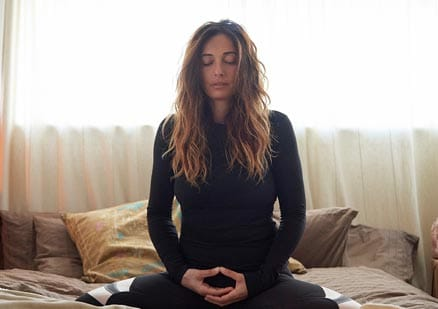 Woman meditating on bed with eyes closed
