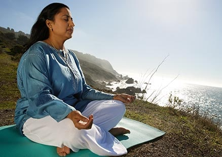woman sitting peacefully in front of the ocean