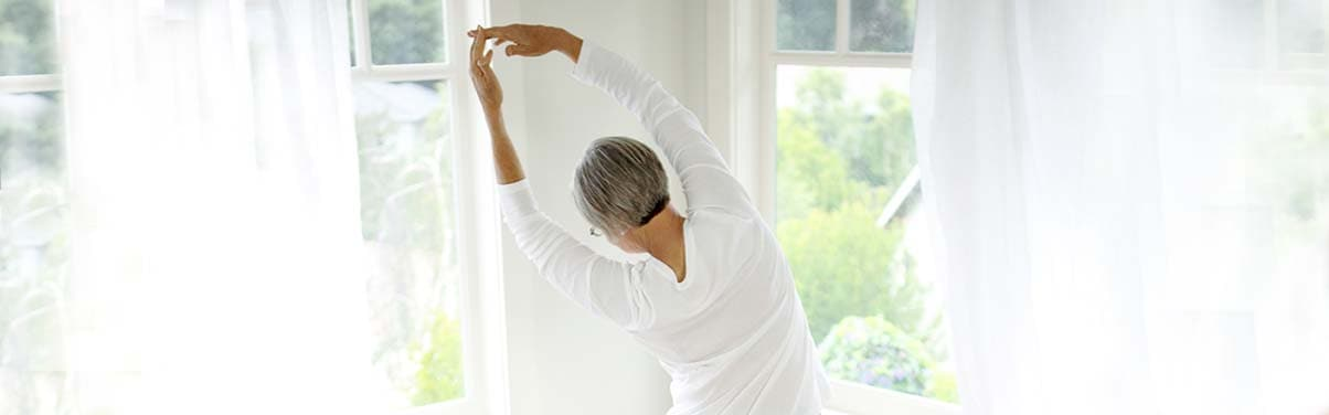 Woman stretching by windows