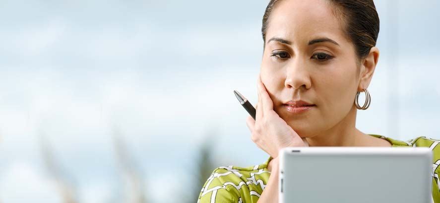 Woman with pen looking thoughtful
